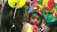 A child in a colourful costume and clown-like make up takes part in the carnival