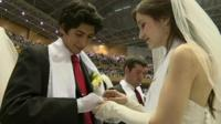 Couple exchanging rings in mass wedding