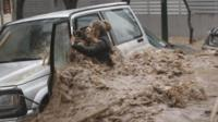 A woman tries to get out of her car in Athens as floodwaters rush past (22 February)