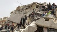 Residents stand in rubble. Rockets struck eastern districts of Aleppo