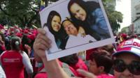 A supporter holds up a picture of Hugo Chavez and his daughters