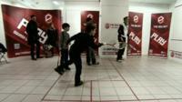 Child plays squash inside a converted shop