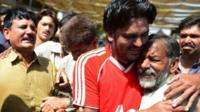 Mourners react during a funeral for bomb blast victims in Karachi