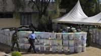Armed security officers guard ballot boxes that have yet to be tallied