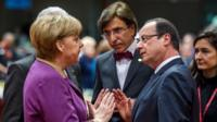 German Chancellor Angela Merkel, peaks with French President Francois Hollande, during a round table meeting at an EU summit in Brussels