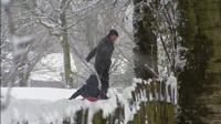 Man pulling a child along on a sledge