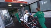 Ambulance staff taking man to A&E