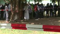 Crowds gather near a mass grave due to be exhumed