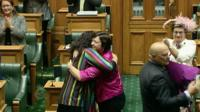 People hugging in New Zealand's parliament after it legalised gay marriage