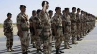 French troops stand at attention during a handover ceremony of the Timbuktu mission from France to Burkina Faso at Timbuktu airport