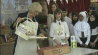 The Duchess of Cornwall watering seeds with school children.