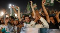 Supporters wave as they greet former Pakistani Prime Minister, Nawaz Sharif, during his campaign closing rally in Lahore
