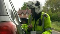 Police officers talks to driver in car