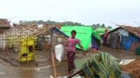 girl walks through makeshift camp