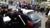 Peppe Pesce being put into a police car