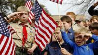 """Joshua Kusterer, 12, Nach Mitschke, 6, and Wyatt Mitschke, 4, salute as they recite the pledge of allegiance during the """"Save Our Scouts"""