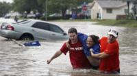 Marco Fairchild, left, and Gary Garza, right, help Sueann Schaller from her car Saturday, May 25, 2013 in San Antonio after she drove it into floodwaters
