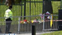 A police officer looks at floral tributes as he guards the scene of a terror attack in Woolwich