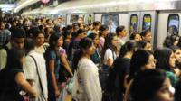 Passengers wait to get onto the Delhi Metro