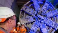 Crossrail construction workers stand near to one of the 1,000 tonne tunnel boring machines to mark the breakthrough into the Canary Wharf station
