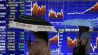 People walk past stock market boards