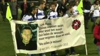 Boys hold a banner with a pictures of Richard Neiuwenhausen on it.