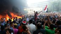 """Opponents of Egypt""""s Islamist President Mohammed Morsi chant slogans as fire rages at the Muslim Brotherhood headquarters in Alexandria"""