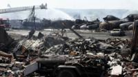 Firefighters at scene of burnt-out train wreckage