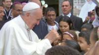 Pope Francis smiles and gives a thumbs-up to children he has just blessed
