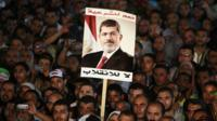 Supporters of deposed Egyptian President Mohamed Morsi hold up a poster of Morsi during a protest at the Rabaa al-Adawiya square where they are camping, in Cairo, 6 August, 2013.