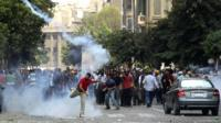 A supporter of ousted President Mohamed Morsi throws a tear gas canister back towards the police during clashes in central Cairo August 13, 2013