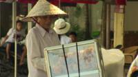 A Vietnamese vendor, selling goods on a street