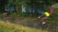 Cyclists riding past a Hackney sign