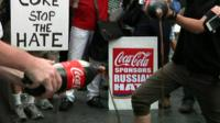 Demonstrators pour Coca Cola down a drain in New York
