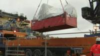 The wreckage being lifted by crane