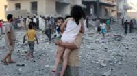 A man carries two children away from the scene of an explosion in the northern Syrian city of Raqqa