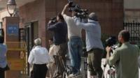 Photojournalists take pictures of a Delhi police van believed to be carrying the accused