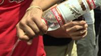Man pours away Stolichnaya vodka