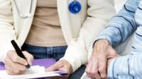 GP and elderly patient filling in form