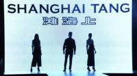 Models walk in front of Shanghai Tang logo