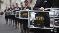 Publicity shot of British Airways cabin crew holding see-through briefcases with Solo book inside