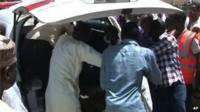 Family members gather outside a vehicle carrying a corpse in Damaturu on 29 September