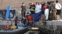 Rescuers lift a body bag as they reach the port of Lampedusa