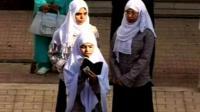 Three Muslim girls reading the Quran