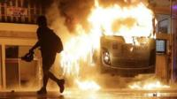 Man walks past a burning bus in Rio de Janeiro