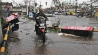 A motorcyclist rides past fallen traffic signal poles in Berhampur, India