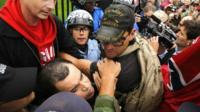 Protesters try to disengage some of their fellow demonstrators from a confrontation with law enforcement as they climb the wall and fence in front of the White House gates in Washington,