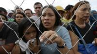 Residents queue up to receive treatment and relief supplies at Tacloban airport Monday