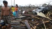 Survivors walk along debris from damaged homes at typhoon ravaged Tacloban