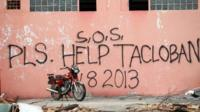 A message seeking help is written on the wall of destroyed building by residents on November 13, 2013 in Tacloban, Leyte, Philippines